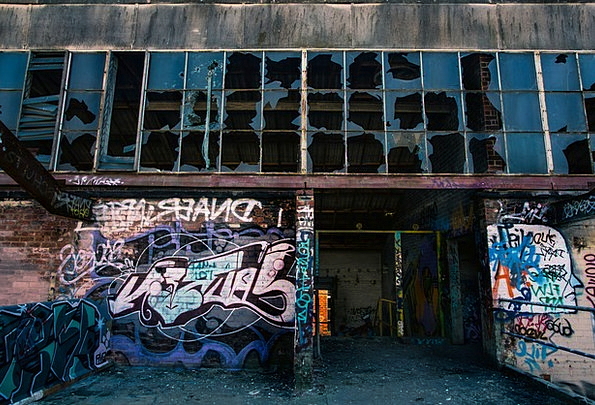 A building with broken windows and spray paint graffiti